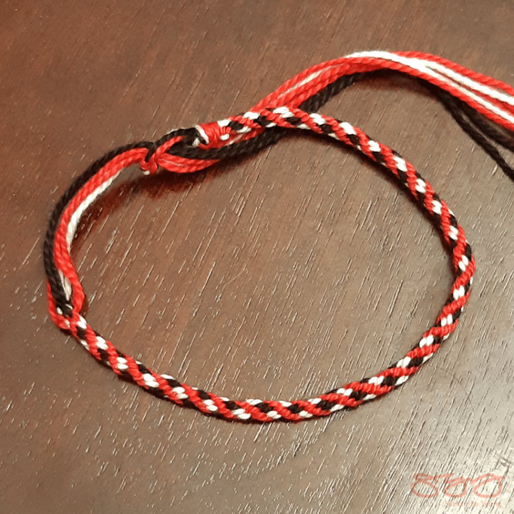 A red, white, and black braided bracelet.