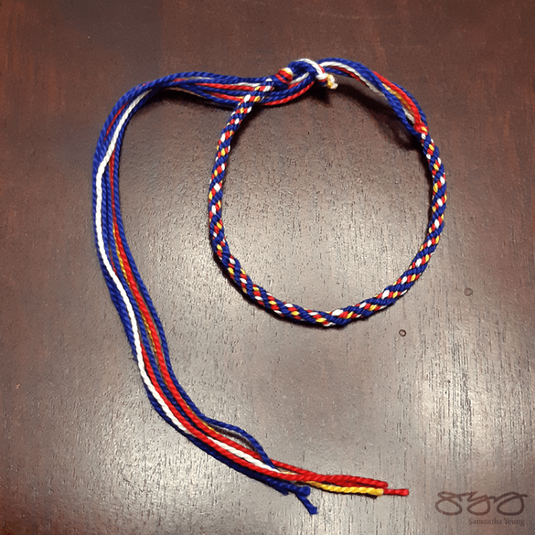 Red, blue, white, and yellow braided kumihimo bracelet. Inspired by Victory Valkyrie.